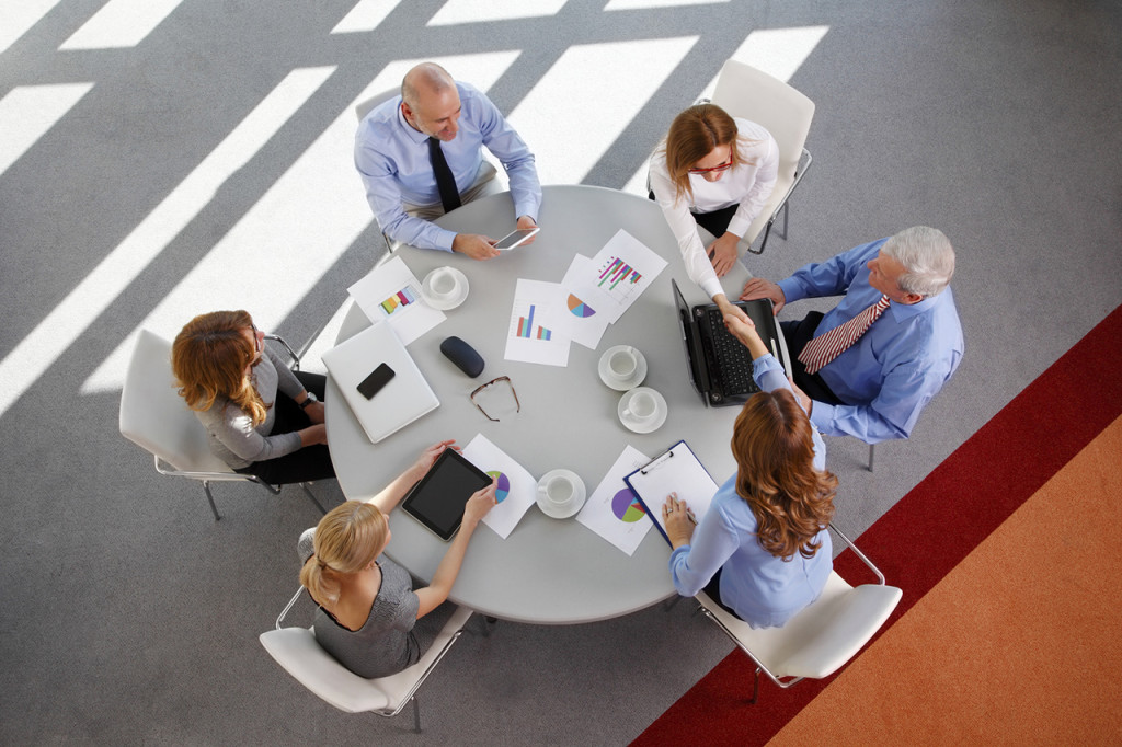 Image from above of business people sitting around the desk and working on presentation. Teamwork at office.